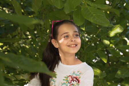 Happy beautiful young girl in white t-shirt and sunglasses on her head among green leaves