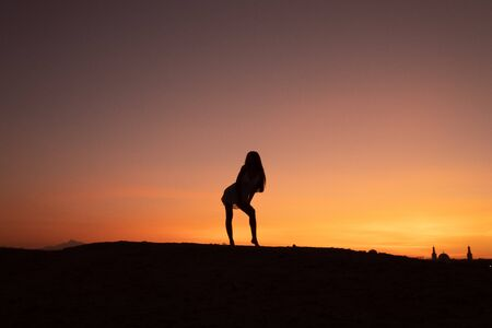 Silhouette of young woman with loose haire in front of the sunset among the desert, colorful sky on the background