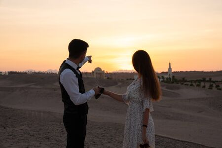 Handsome young man in white shirt holds the hand of his girlfriend and pointing at sunset, romantic couple in elegant clothes standing among the desert and enjoying sunset Archivio Fotografico