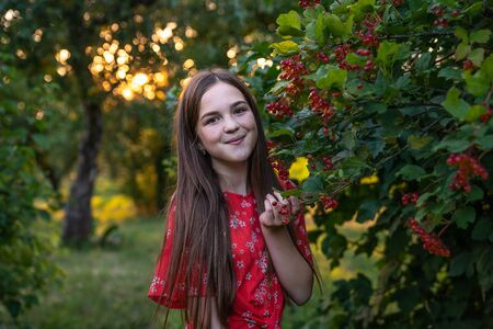 Beautiful teen girl with red hair and freckles peeping from behinde a bush of viburnum