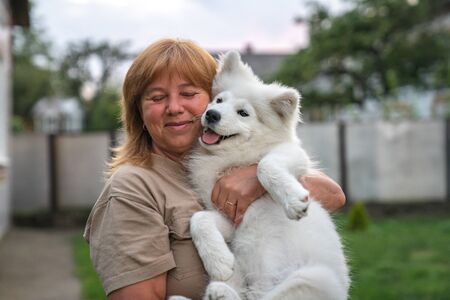 Happy blonde haired woman with closed eyes hugs white smoyed puppy