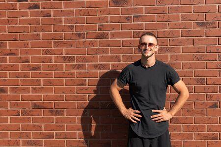 Felice giovane uomo attraente in occhiali da sole, vestito con una maglietta nera in piedi con le mani su una cintura, muro di mattoni rossi sullo sfondo