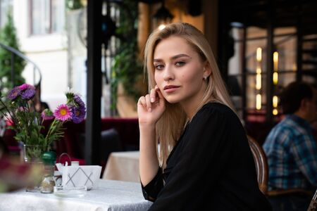 Mysterious blond girl in black dress sitting at a table in a cozy street cafe decorated with flowers and straightens hair with her hand Foto de archivo