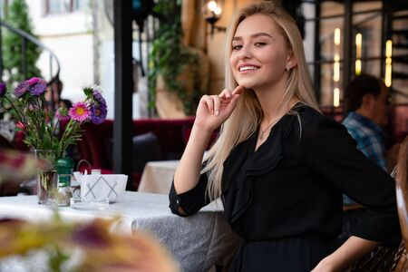 Attractive blonde gil with loose hair and natural make up, dressed in black dress sitting at a table in a cozy street cafe decorated with flowers Banco de Imagens