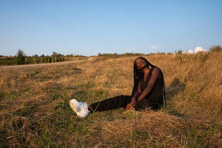 Young african girl in black clothes sits with clothed eyes on the ground among the dry grass field