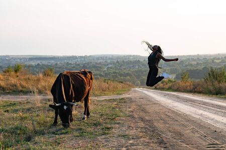 Happy african girl in black clothes jump on a dirt road, cow graze near the girl