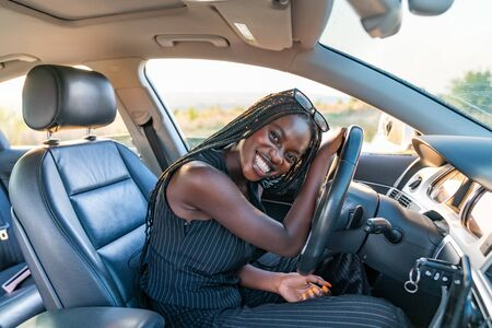Heureuse fille africaine souriante en vêtements rayés noirs conduit une voiture Banque d'images