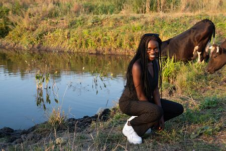 Happy smiling african girl in black clothes crouched and looking at the camera, cow drinks water from the lake on the background