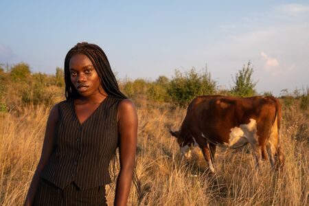 Waist up portrait of the young african girl in black clothes stands among the dry grass field and looking at the camera, cow graze on the background