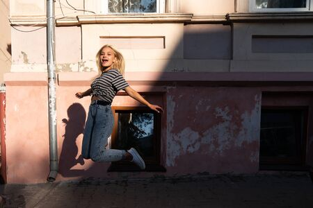 Happy excited blonde teen girl with loose hair dressed in casual clothes jumping among the street of the old city Archivio Fotografico