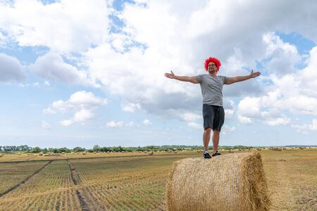 Young man in red wig stands on the round haystack with wide open hands and looking awya, sky with clouds on the background