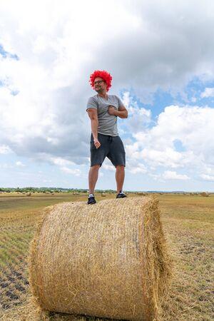 Starker junger Mann in roter Perücke steht auf dem runden Heuhaufen im Feld und zeigt seinen Trizeps