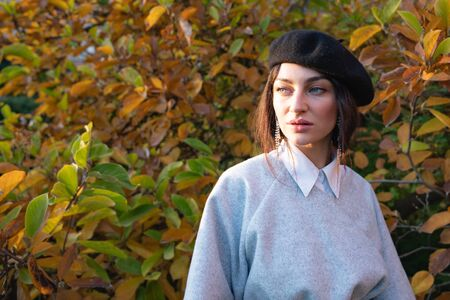 Waist up portrait of the beautiful excited girl with natural makeup in black beret and grey dress, autumn tree on the background