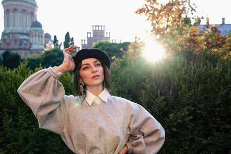 Waist up portrait of the young attarctive female in black beret and grey dress holds one hand on her waist other hand near her head, sunset on the background