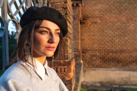 Close up portrait of the beautiful girl with natural makeup and blue eyes, dressedd in black beret, brick wall on the background