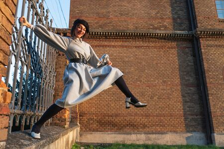 Happy smiling girl in black beret and grey dress holds on to the fence with one hand, keeps her foot in the air, brick red wall on the background