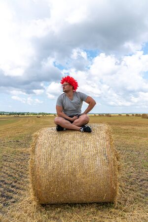 Young man in red wig and glasses, dressed in grey t-shirt sits on the round haystack in lotus position among the field