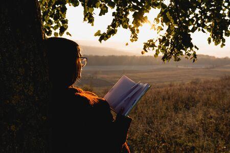 Jolie jeune fille brune en pull rouge s'est penchée sur un grand arbre, tient le livre à la main et regarde le coucher de soleil Banque d'images