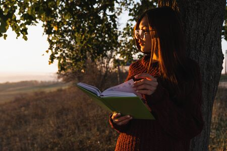 Young brunette girl in red sweater and glasses leaned on a big tree with book in hands, enjoying weekend among autumn meadow, sunny day