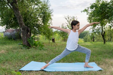 Attractive brunette girl in white undershirt practicing yoga, standing in warrior two exercise, virabhadrasana 2 pose, working out on a blue mat among the park