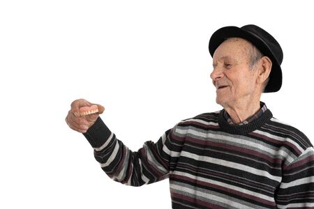 Side view portrait of the happy old man in casual clothes and black hat, senior holds denture in hand and looking at it, isolated over wite background