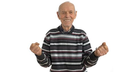 Waist up portrait of the old man in casual clothes, senior is very happy and excited doing winner gesture with arms raise, looking at the camera, isolated over white background. Celebration concept Reklamní fotografie