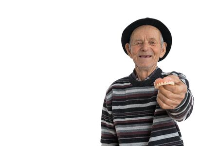 Waist up portrait of the old happy man in black hat showing model of human teeth and looking at the camera, isolated over white background