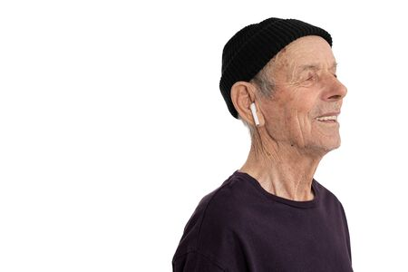 Cerrar vista lateral retrato del elegante anciano con sombrero negro y auriculares inalámbricos blancos en la oreja derecha, aislado sobre fondo blanco, copyspace