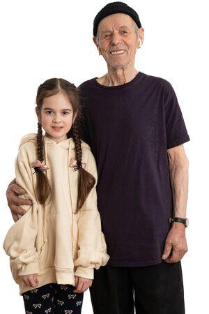 Atrakcyjny uśmiechnięty staruszek w czarnym kapeluszu, koszulce i białych słuchawkach bezprzewodowych, starszy pencjoner patrzący w kamerę i przytulający swoją wnuczkę ubraną w beżową bluzę z kapturem, biała ściana na tle