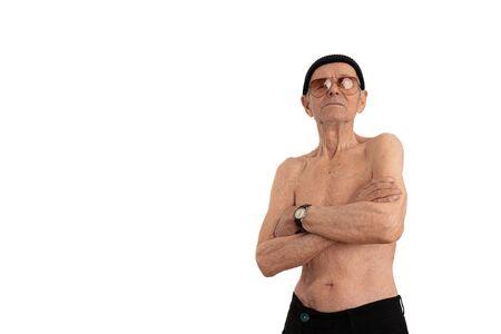 Anciano sin camisa confiado y tranquilo con sombrero negro y gafas de sol, elegantes soportes de alto nivel con las manos cruzadas y mirando a la cámara aislada sobre fondo blanco, copyspace para su texto
