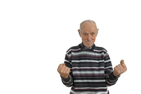 Waist up portrait of the old man in casual clothes, senior is very happy and excited doing winner gesture with arms raise, looking at the camera, isolated over white background. Celebration concept