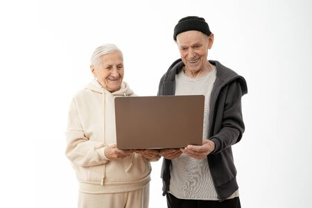 Couple of stylish seniors in casual clothes smiling and looking at the same laptop hugged isolated over white background - indoor, at home concept - european mature and retired man and woman using technology, copyspace