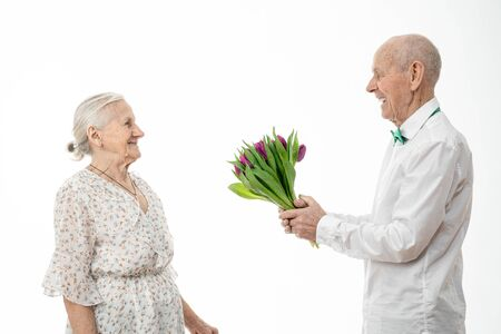 Senior man in white shirt holding flowers in hands on a date with an elderly woman in white dress isolated on white background, old husband gives a bouquet of tulips to his wife