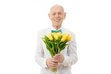 Happy, glad, cheerful, joyful smiling old man in white shirt, senior holds bouquet of yellow flowers in hands and looking at the camera isolated over white background, copyspace for your text - Womens day, St. Valentines day concept