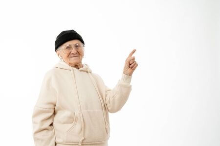 Stylish serous old woman in beige hoodie, black hat and glasses pointing at the upper right corner and looking at the camera isolated over white background, copyspace