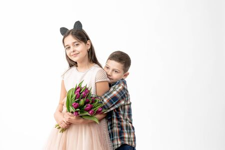 Handsome little boy in shirt hugging his cheerful cute sister in beige dress, brunette girl holds purple flowers in her hands and looking at the camera, isolated over white background Archivio Fotografico - 140883536
