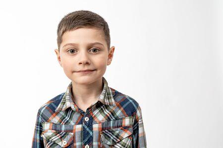 Retrato de cerca del niño guapo confiado en camisa que mirando a la cámara aislada sobre fondo blanco, copyspace para su texto Foto de archivo