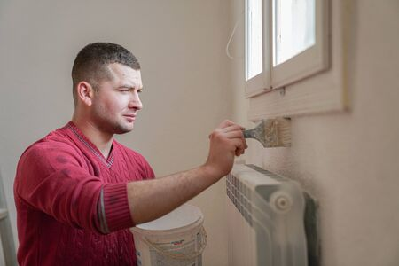 Construction worker and handyman doing finish renovation at apartment. Professional painter using paint roller brush painting of wall with white color on construction site. Standard-Bild