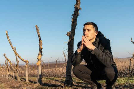 Close up photo of the young unhappy, sad man in black clothes that crouched among his old garden with sawn trunks and praying, holds his hands near his face, blue sky on the background