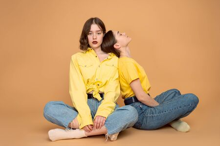 Tired young girls in casual clothes sitting on the ground, leaned on each other, isolated over orange background