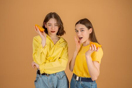 Beautiful girls in yellow shirts standing together against orange background and holding sliced orange in hands, looking at the camera