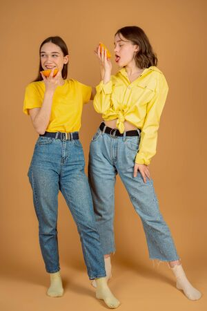 Two attractive brunette girls in casual clothes eating sliced orange while standing together against orange wall