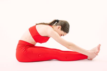 Fit woman in red sportswear stretching her legs to warm up - isolated over white background, healthy lifestyle concept Reklamní fotografie