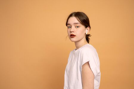 Serious girl with red lips wearing wireless headphones, looking at the camera isolated over orange background with copyspace