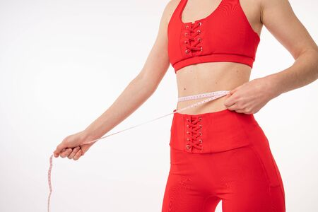 Beautiful young woman in red sportswear with measuring tape on white background. Weight loss concept Фото со стока
