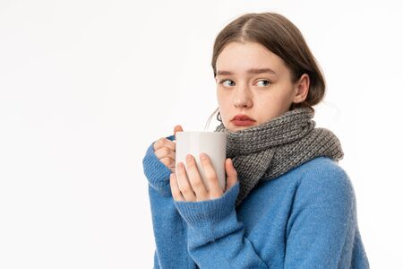 Flu treatment. Portrait of sick brunette teenage girl wearing casual clothes and scarf, holding cup of tea, studio shot isolated on white background Stockfoto