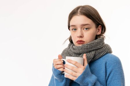 Portrait of an upset girl dressed in sweater and scarf isolated over white background, holding cup of hot tea