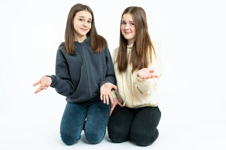 Indignant young girls in casual clothes crouched, looking at the camera and shrugging, isolated over white background