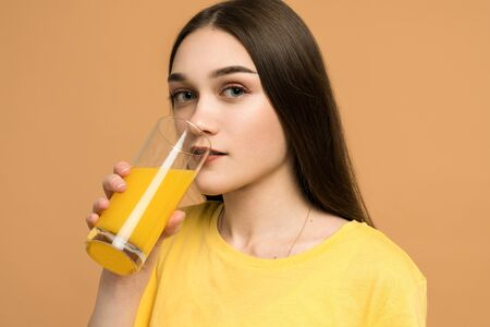 Portrait of a cute casual girl drinking orange juice from a glass and looking at camera isolated over yellow background