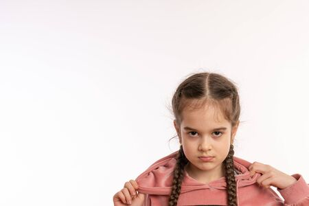 Close up photo of an upset, angry little girl with pigtails isolated over white background Foto de archivo